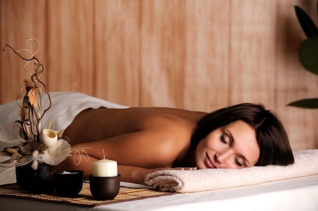 Mujer hermosa joven relajarse en el salón de spa