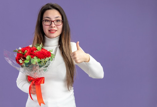 Mujer hermosa joven en ropa casual sosteniendo un ramo de rosas rojas mirando a la cámara feliz y positivo mostrando los pulgares para arriba el concepto del día de san valentín de pie sobre la pared púrpura