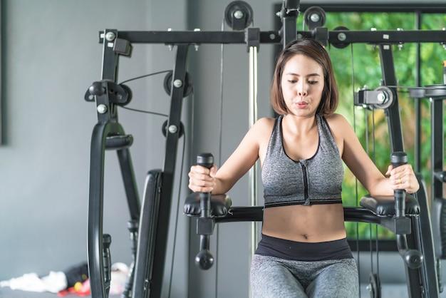 Mujer hermosa joven en la ropa de deportes que se resuelve en gimnasio