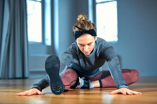 Mujer hermosa joven en ropa deportiva haciendo estiramientos mientras está sentado en el piso frente a la ventana en el gimnasio
