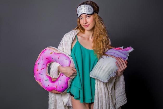 Mujer hermosa joven en ropa de dormir con almohadas divertidas