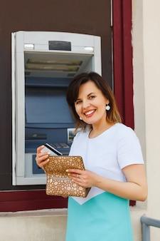 Mujer hermosa joven saca una tarjeta de banco