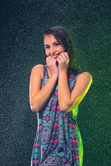 Mujer hermosa joven bajo salpicadura de lluvia