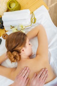 Mujer hermosa, joven y saludable en el salón de spa. tratamiento de masaje