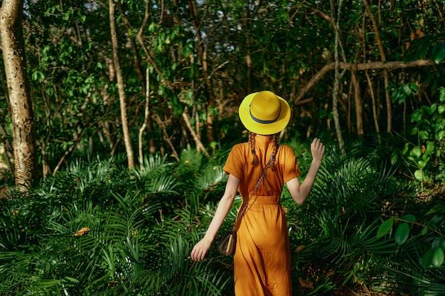 Mujer hermosa joven en la selva tropical con sombrero camina en el parque, naturalista
