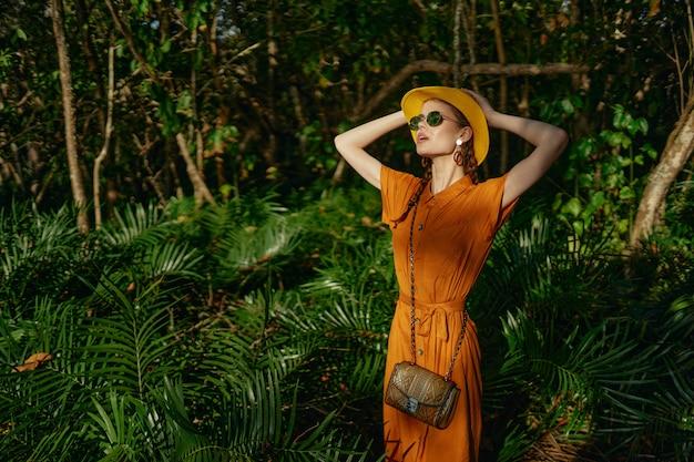 Mujer hermosa joven en la selva tropical con sombrero camina en el parque