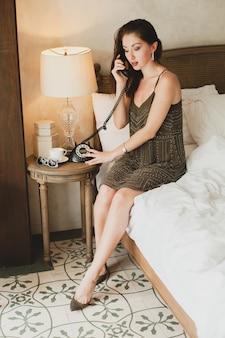 Mujer hermosa joven sentada en la cama en el hotel, elegante vestido de noche, estado de ánimo sensual, hablando por teléfono, sonriendo, coqueta, mirando, sexy