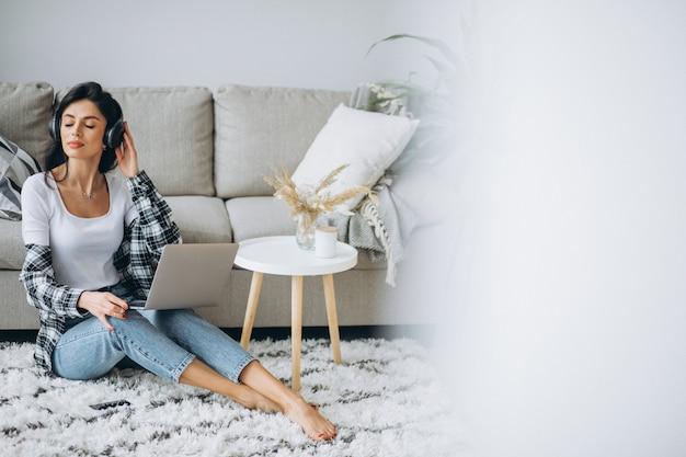 Mujer hermosa joven sentada en casa trabajando en la computadora portátil en los auriculares