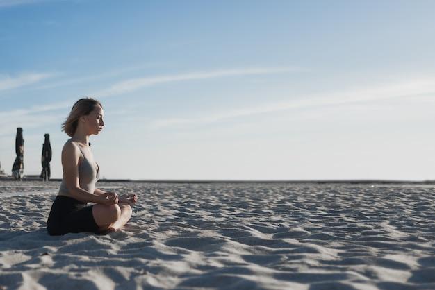 Mujer hermosa joven se sienta en la arena y medita