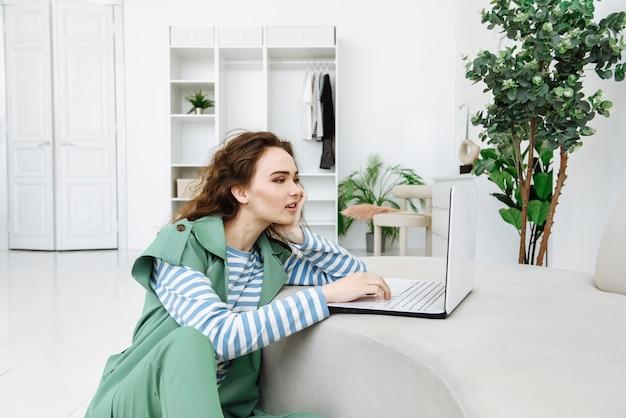 Mujer hermosa joven se sienta con una computadora portátil en la escena del interior de la casa y realiza compras en línea o trabaja desde casa a través de internet