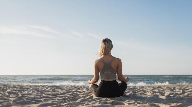 Mujer hermosa joven se sienta en la playa