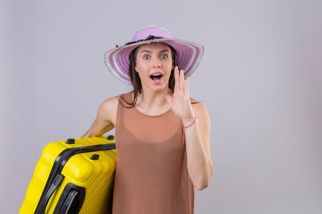 Mujer hermosa joven en el sombrero del verano que sostiene la maleta amarilla que llama a alguien con la mano cerca de la boca que se coloca sobre el fondo blanco