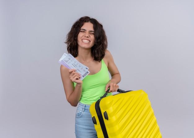 Mujer hermosa joven sonriente del viajero que sostiene los billetes de avión y la maleta en la pared blanca aislada con el espacio de la copia