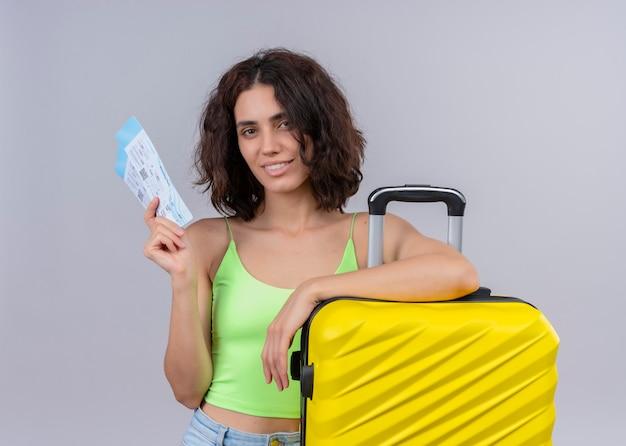 Mujer hermosa joven sonriente del viajero que sostiene los billetes de avión y la maleta en la pared blanca aislada