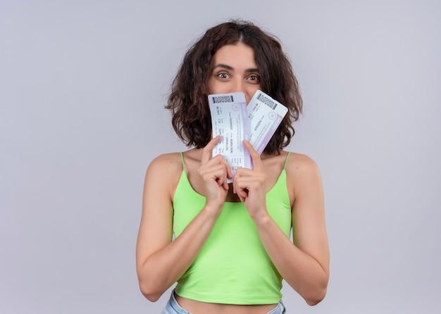 Mujer hermosa joven sorprendida que sostiene los billetes de avión en la pared blanca aislada