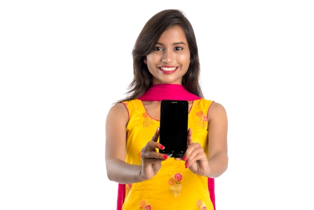 Mujer hermosa joven sosteniendo y mostrando un teléfono inteligente con pantalla en blanco o un teléfono móvil o tableta
