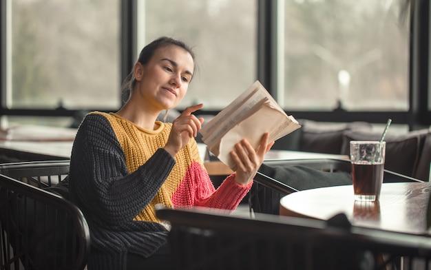 Mujer hermosa joven en suéter anaranjado que lee el libro interesante en café