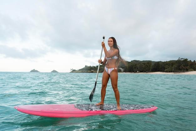 Mujer hermosa joven surfeando en hawaii