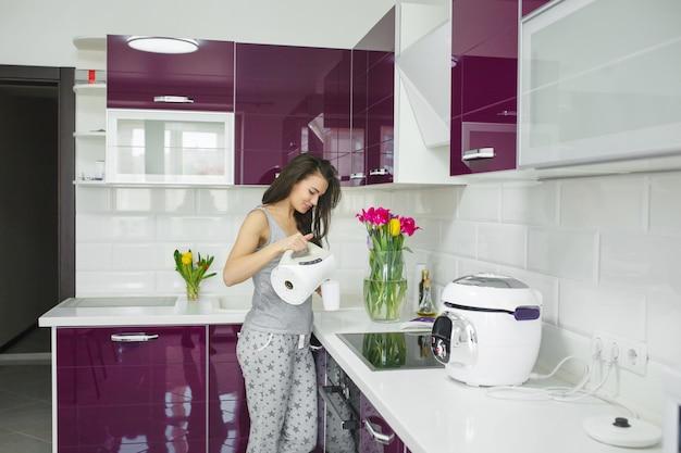 Mujer hermosa joven temprano en la mañana tomando café en la cocina. mañana fresca bebida vigorizante. despierta dama.