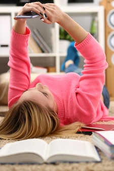 Mujer hermosa joven tiene un descanso acostarse en el piso sostenga el teléfono inteligente en brazos concepto agradable de vacaciones