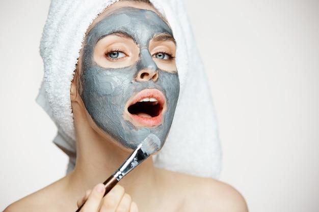 Mujer hermosa joven en toalla en la cabeza que cubre la cara con la máscara con la boca abierta. cosmetología de belleza y spa.