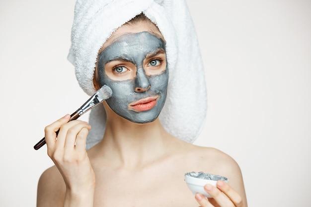 Mujer hermosa joven en toalla en la cabeza que cubre la cara con la máscara sonriendo. cosmetología de belleza y spa.