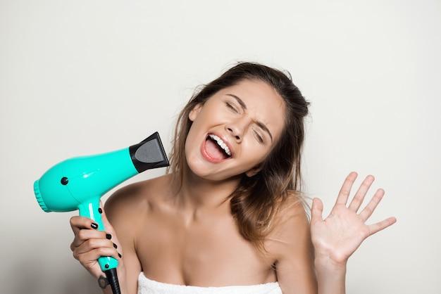 Mujer hermosa joven en toalla cantando con secador de pelo
