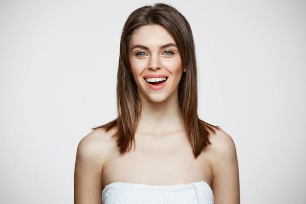 Mujer hermosa joven en toalla con maquillaje natural sonriendo. cosmetología y spa. tratamiento facial.