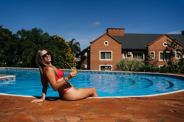 Mujer hermosa joven tomando el sol sentado en el borde de la piscina