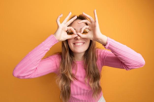 Mujer hermosa joven en top rosa con gafas mirando a través de los dedos haciendo gesto binocular sonriendo de pie sobre fondo naranja