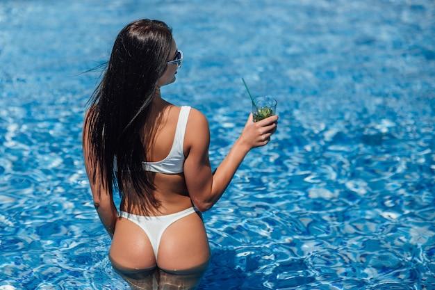 Mujer hermosa joven en traje de baño blanco y gafas de sol