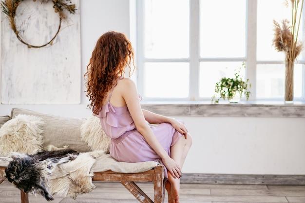 Mujer hermosa joven triste por la ventana
