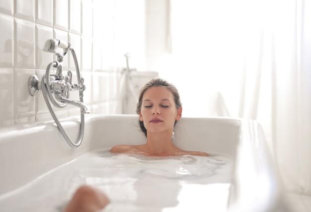Mujer hermosa joven tumbado en una bañera y descansar