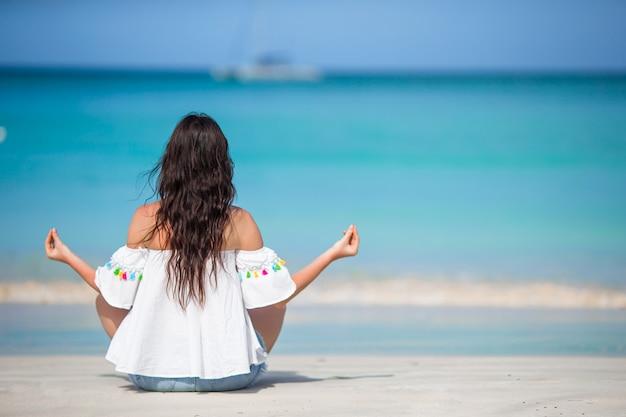 Mujer hermosa joven en vacaciones en la playa en caribes