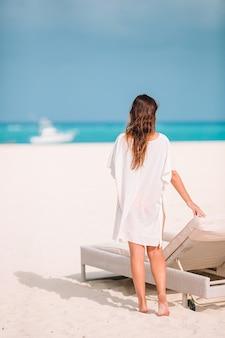 Mujer hermosa joven en vacaciones en la playa en caribs
