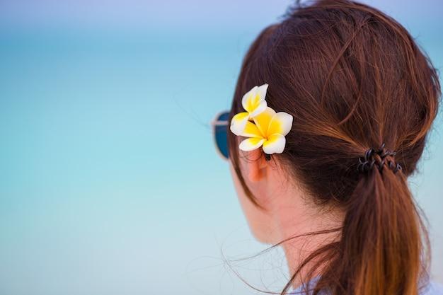 Mujer hermosa joven durante vacaciones en la playa tropical. disfruta de unas vacaciones de verano solo en la playa de áfrica con flores de frangipani en el pelo