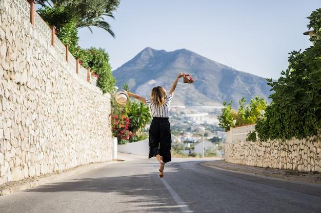 Mujer hermosa joven en vacaciones saltando. en una mano sandalias en el sombrero de segunda mano.