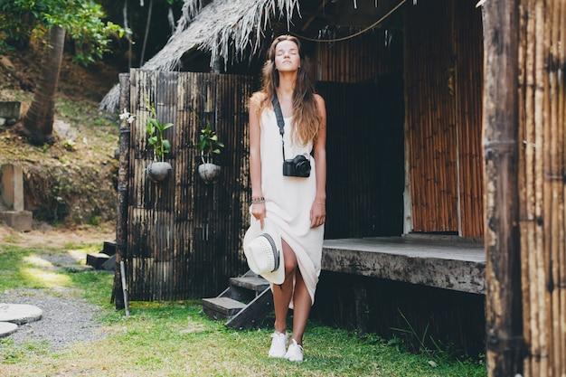 Mujer hermosa joven en vacaciones tropicales en asia, estilo veraniego, vestido blanco boho, zapatillas, cámara de fotos digital, viajero, sombrero de paja, relajado