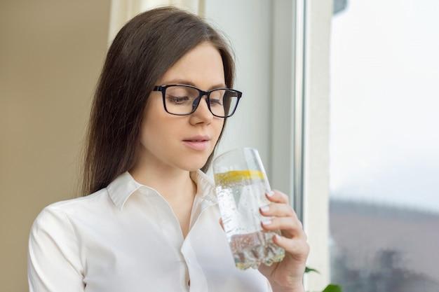 Mujer hermosa joven en vasos con vaso de agua mineral con limón
