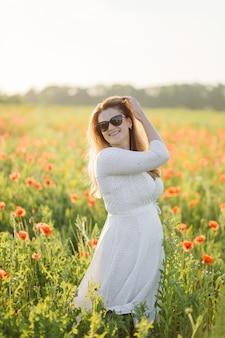 Mujer hermosa joven con vestido blanco posando en un campo de amapolas