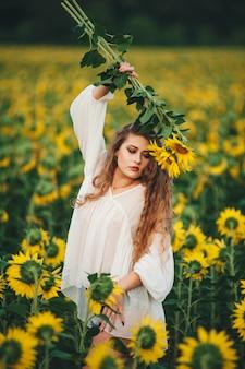 Mujer hermosa joven en un vestido entre los girasoles florecientes. agrocultura.