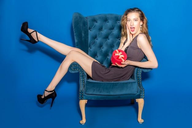 Mujer hermosa joven en vestido gris sentado en un sillón azul con caja de regalo