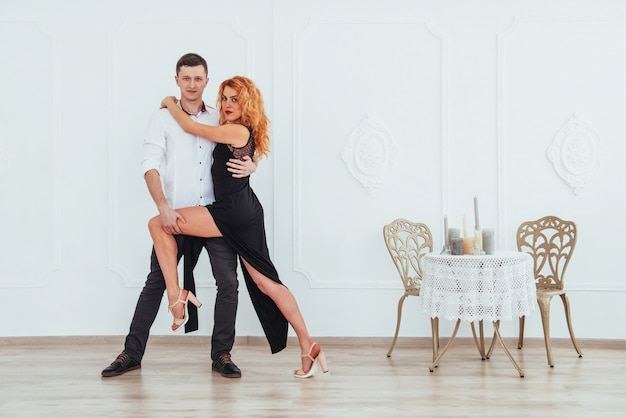 Mujer hermosa joven en un vestido negro y un hombre en camisa blanca bailando.