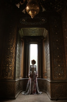 Mujer hermosa joven en vestido rosa posando en palacio de lujo