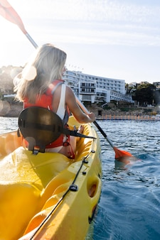Mujer hermosa joven viajando en canoa