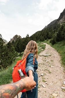 Mujer hermosa joven viajando en las montañas