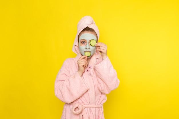 Una mujer hermosa joven de vista frontal en bata de baño rosa con anillos de pepino