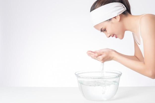 La mujer hermosa se está lavando la cara en el fondo blanco