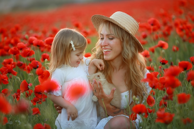 Mujer hermosa mamá rubia con bebé en brazos en el campo de amapolas