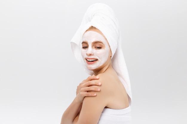Mujer hermosa con la máscara facial en el fondo blanco